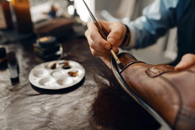 Schuhmacher mit bürstentönungsschuhen, schuhreparaturservice. handwerkskunst, schuhmacherwerkstatt, meisterarbeiten mit stiefeln, schuster