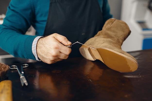 Schuhmacher näht den schuh, schuhreparaturservice
