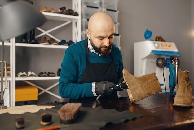 Schuhmacher repariert den schuh, schuhreparaturservice