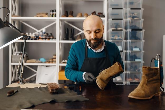 Schuhmacher schärft die schuhsohle, schuhreparaturservice