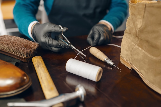 Schuhmacher schneidet den faden, schuhreparaturservice