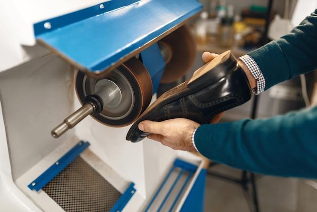 Schuhmacher verarbeitet damenschuhe auf schmirgelmaschine, schuhreparatur. handwerkskunst, schuhmacherwerkstatt, meister arbeitet mit stiefeln