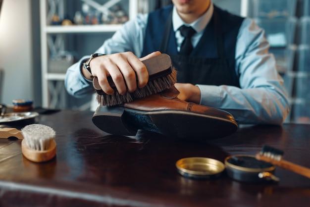 Schuhmacher wischt schwarze schuhcreme ab, reparaturservice für schuhe. handwerkskunst, schuhmacherwerkstatt, meisterarbeiten mit stiefeln, schusterladen