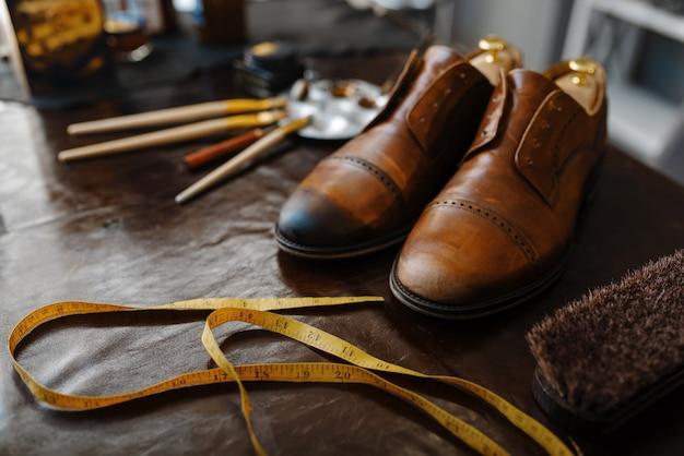 Schuhmacherjob, schuhreparaturservicekonzept. schuhmacherwerkstatt, reparierte stiefel und schuhmacherwerkzeuge auf dem tisch, schusterjob