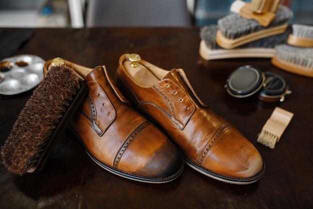 Schuhreparaturservicekonzept, stiefel und politur, schuhmacherarbeitsplatz, niemand. schuhmacherwerkstatt, repariertes schuhwerk auf dem tisch, schusterarbeit