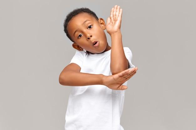 Schul-, kinder-, lern- und bildungskonzept. hübscher, selbstbewusster, dunkelhäutiger, ausgezeichneter schüler, der die hand hebt, als würde er im unterricht am schreibtisch sitzen, wissen demonstrieren und fragen beantworten
