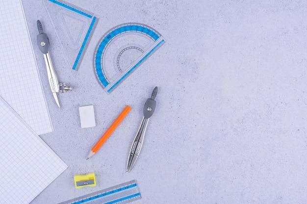 Schul- oder bürowerkzeuge mit haftnotizen auf grau.