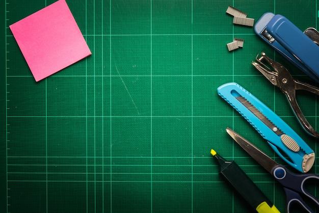 Schul- und büroartikelrahmen, auf schneidendem mattenbretthintergrund