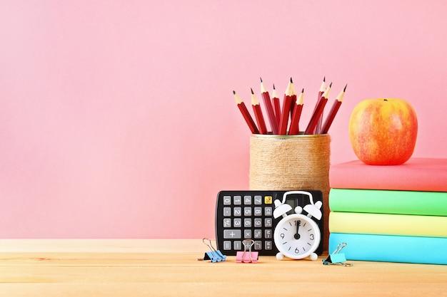 Schul- und bürobedarf auf einem rosa hintergrund. zurück zur schule.