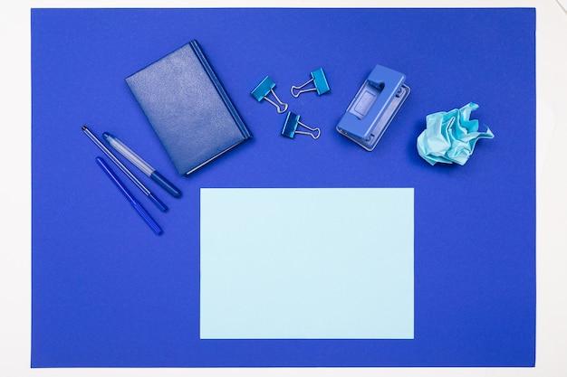 Schul- und büromaterial liegen ordentlich an einer blauen wand
