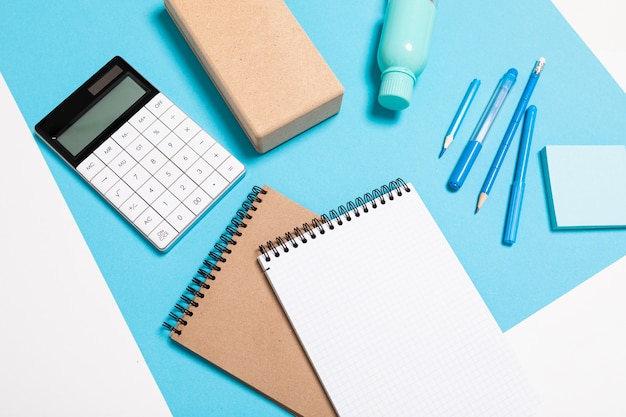 Schul- und büromaterial liegen ordentlich an einer weiß-blauen wand