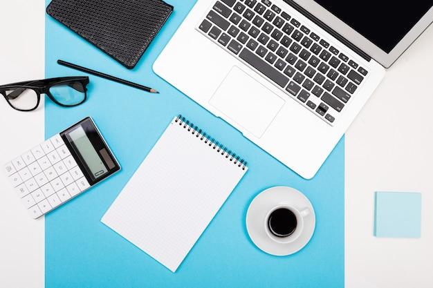 Schul- und büromaterial liegen ordentlich auf weiß und blau