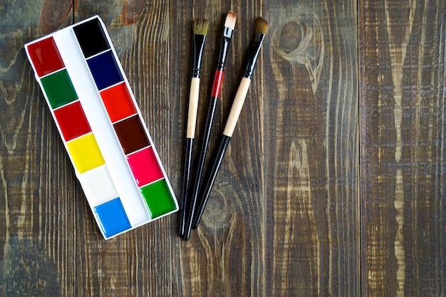 Schulaquarellzubehör und -bürsten für das malen auf einem dunklen hölzernen hintergrund mit kopienraum. ansicht von oben