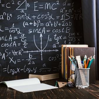 Schulbank im klassenzimmer, mit büchern auf hintergrund der tafel mit schriftlichen formeln