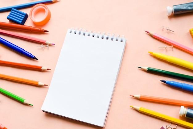 Schulbedarf am notizbuch auf einem rosa hintergrund.