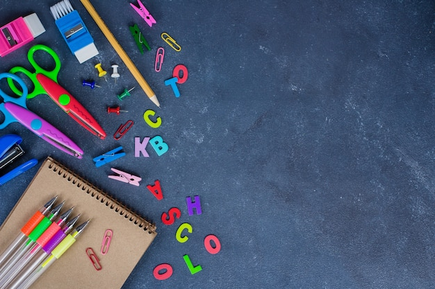 Schulbedarf auf dem tafelhintergrund bereit zu ihrer auslegung