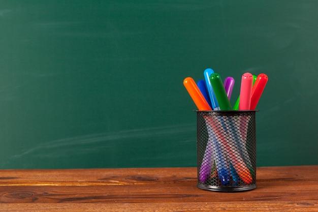 Schulbedarf auf einem holztisch- und tafelhintergrund