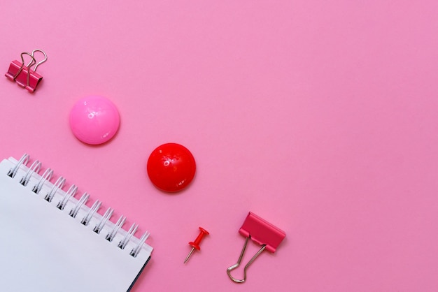 Schulbedarf auf einem rosa hintergrund tafel hintergrund bereit für ihr design inschrift notizbuch
