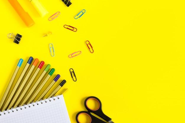 Schulbedarf auf gelbem hintergrund mit copyspace für design. bleistifte, scheren, draufsicht des notizbuches