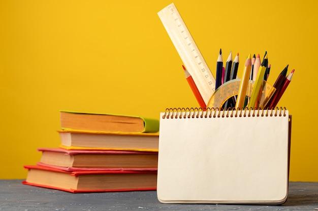 Schulbedarf auf hölzernem schreibtisch gegen gelbe hintergrundvorderansicht