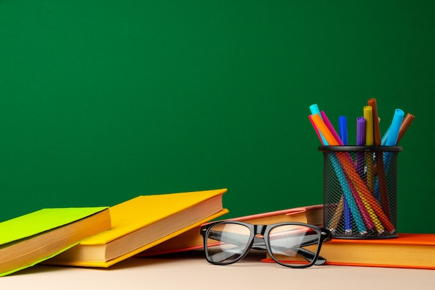 Schulbedarf auf hölzernem schreibtisch gegen vorderansicht der grünen tafel