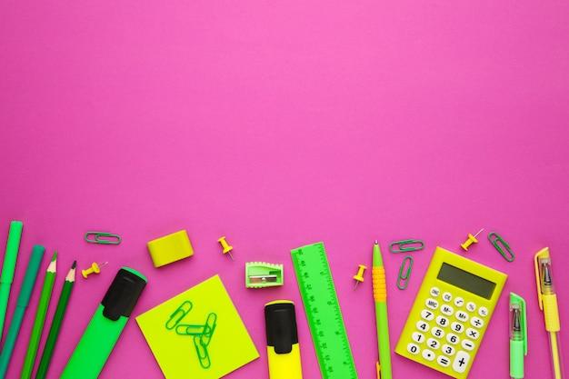 Schulbedarf auf rosa hintergrund mit kopienraum. zurück zur schule. flach liegen.