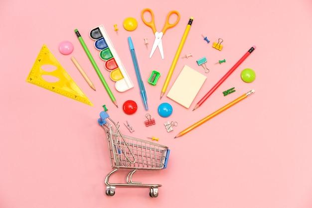 Schulbedarf auf rosafarbener oberfläche in einkaufswagenansicht von oben kopierraumbüro