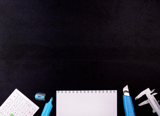 Schulbedarf auf schwarzem bretthintergrund. zurück zum schulkonzept