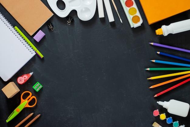 Schulbedarf auf tafelhintergrund. zurück zum schulkonzept. rahmen, flatlat, kopierraum für text