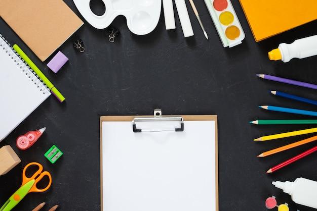 Schulbedarf auf tafelhintergrund. zurück zum schulkonzept. rahmen, flatlay, kopierraum für text. attrappe, lehrmodell, simulation