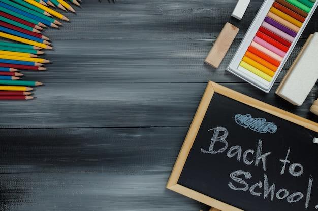 Schulbedarf auf tafelhintergrund. zurück zum schulkonzept.