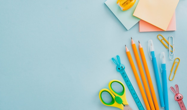 Schulbedarf briefpapier auf blau, zurück zum schulkonzept mit kopierraum für text, flach gelegt