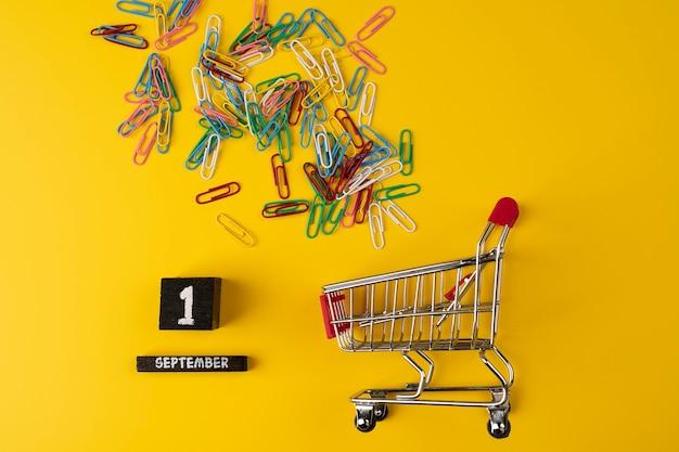 Schulbedarf in einem einkaufswagen und kalender mit datum 1. september auf gelbem hintergrund