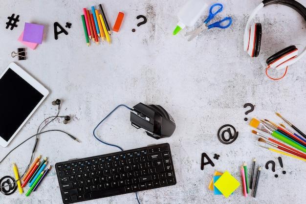 Schulbedarf mit tablet und computertastatur auf weißem tisch. zurück zum schulkonzept.
