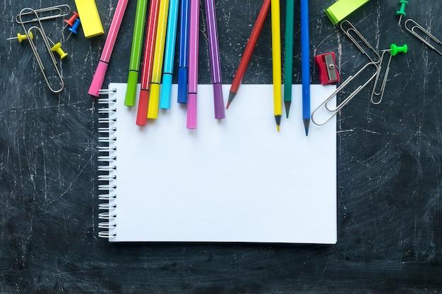 Schulbedarf und notizbuch auf einem tafelhintergrund. freier platz für text