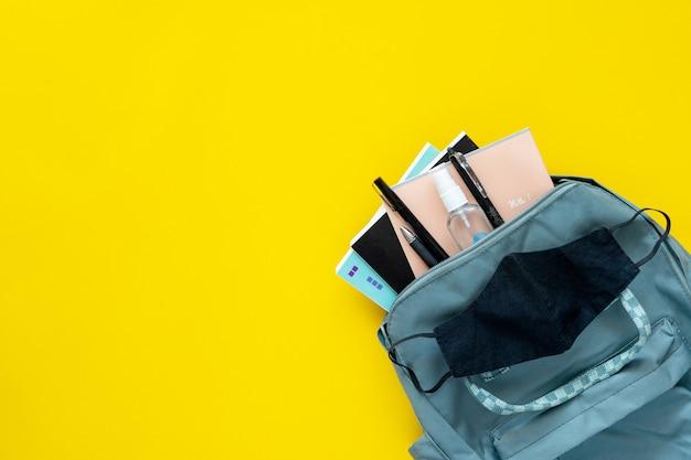 Schulbedarf und schulrucksack auf gelbem grund mit schutzmaske und antibakteriellem...