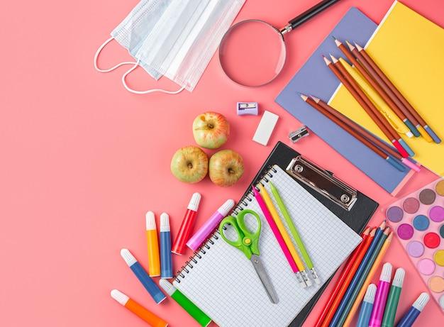 Schulbedarf und schutzmasken auf einem rosa hintergrund-draufsicht-kopierraum