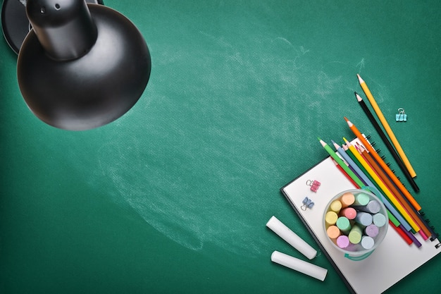 Schulbedarf und schwarze tischlampe auf grünem brett. konzept zurück in die schule. mock-up für design. platz kopieren. bildungskonzept.
