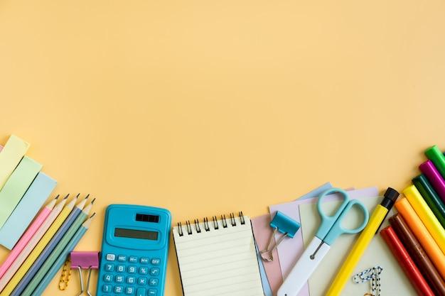 Schulbedarfbriefpapierausrüstung auf farbhintergrund mit kopienraum