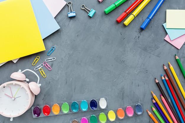 Schulbedarfsbriefpapier, bleistifte, farben, papier auf grauem hintergrund