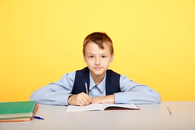 Schulbildung konzept. junge, der am tisch sitzt und isoliert im gelben klassenzimmer studiert.