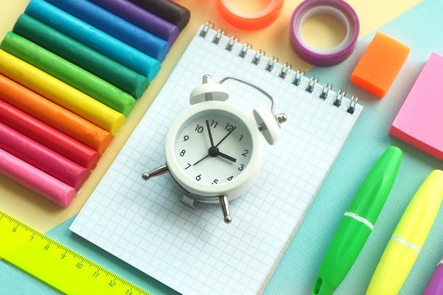 Schulbriefpapier: plastilin, marker, notizblock, lineal, aufkleber, klebeband und ein weißer wecker auf gelb-blauem grund.