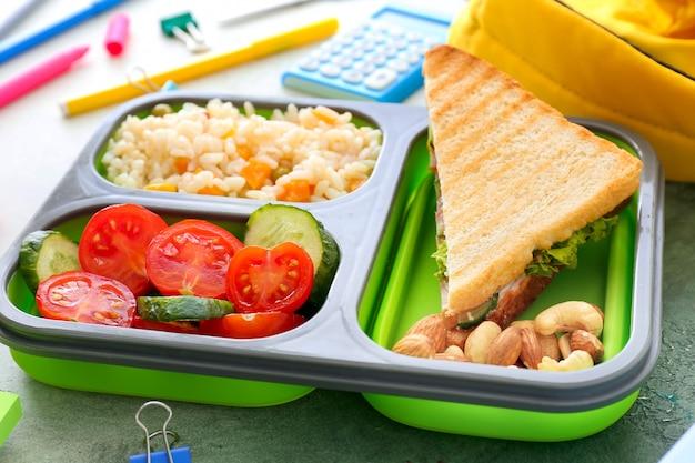 Schulbrotdose mit leckerem essen auf dem tisch