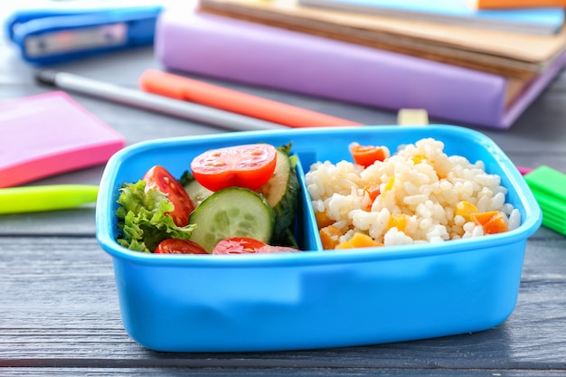 Schulbrotdose mit leckerem essen auf holz