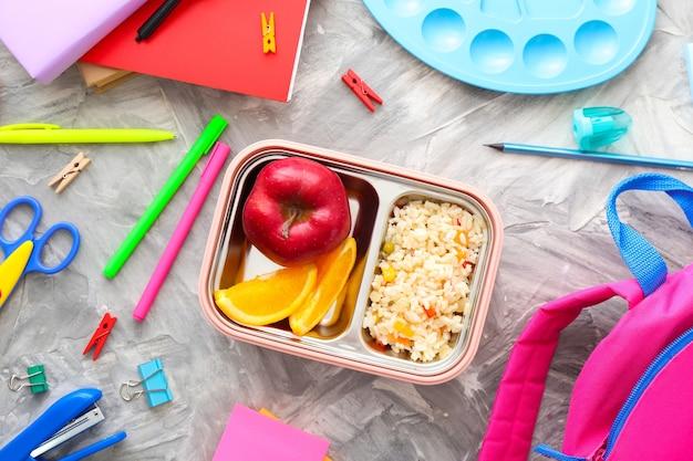 Schulbrotdose mit leckerem essen und briefpapier auf grau
