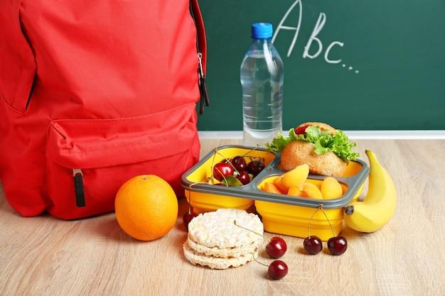 Schulbrotdose mit leckerem essen und rucksack auf dem tisch im klassenzimmer
