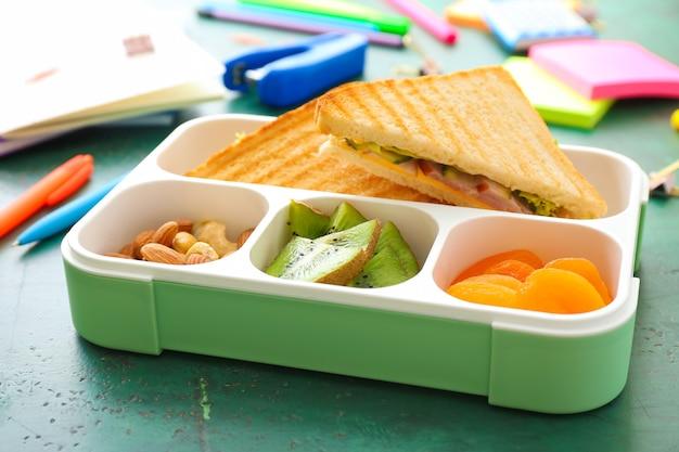 Schulbrotdose mit leckerem essen und schreibwaren auf dem tisch