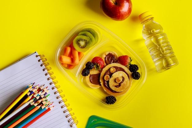 Schulbrotdose mit pfannkuchen, frischem obst und einer flasche wasser.