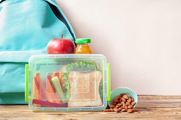 Schulbrotdose mit sandwich, gemüse, saft und mandeln auf tabelle.