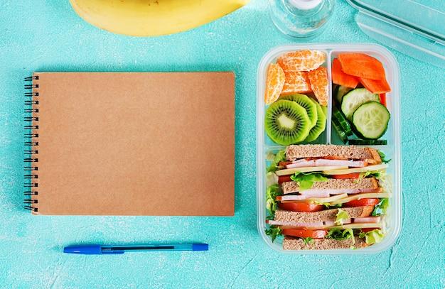 Schulbrotdose mit sandwich, gemüse, wasser und früchten auf tabelle. gesundes essgewohnheitskonzept. flach liegen. ansicht von oben